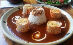 This is chicken wrapped in rice and red mole.