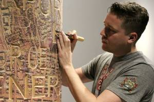 Tim Laidler carves the surface of a tribute pole being created by veterans. Photo: YOLANDE COLE
