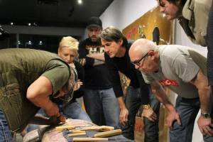 Xwalacktun leads a carving lesson as participants in the veterans tribute-pole project observe. Photo: YOLANDE COLE