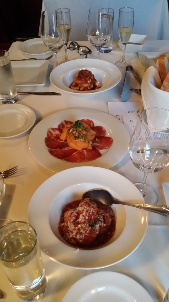 Appetizer of grilled calamari in rich tomato sauce, 2 year aged proscuitto with melon & pickled garnish and meatballs in sauce.