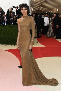 Zendaya keeps it simple yet impactful in a gilded one-shoulder Michael Kors gown with a train and turtleneck detail.