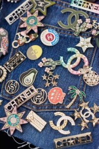 clusters of CHANEL pins on denim jacket