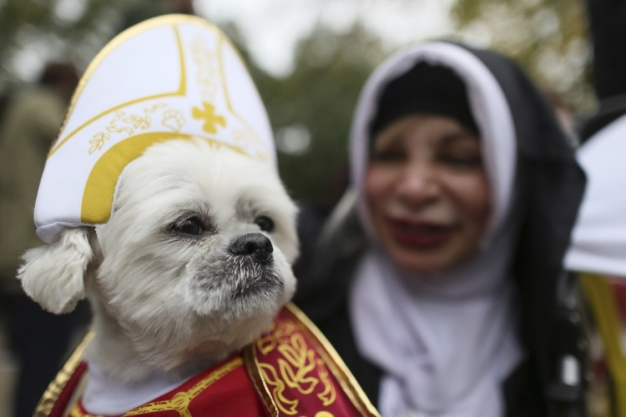 Michelle Guillen and her shih tzu Jojo wear a Pope and a nun costume as they participate in the annual Tompkins Square Halloween Dog Parade. AP Photo/Mary Altaffer