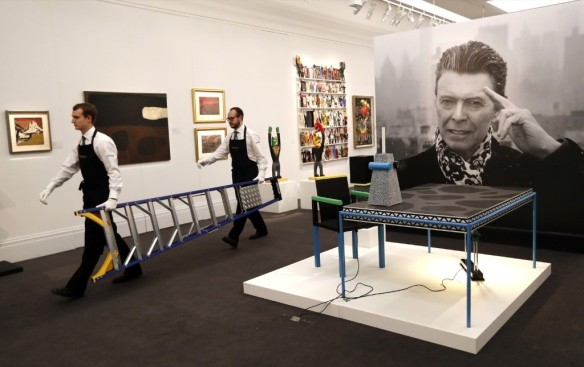 Technicians prepare artworks from the Bowie Collection to go on display at Sotheby's. AP Photo/Kirsty Wigglesworth